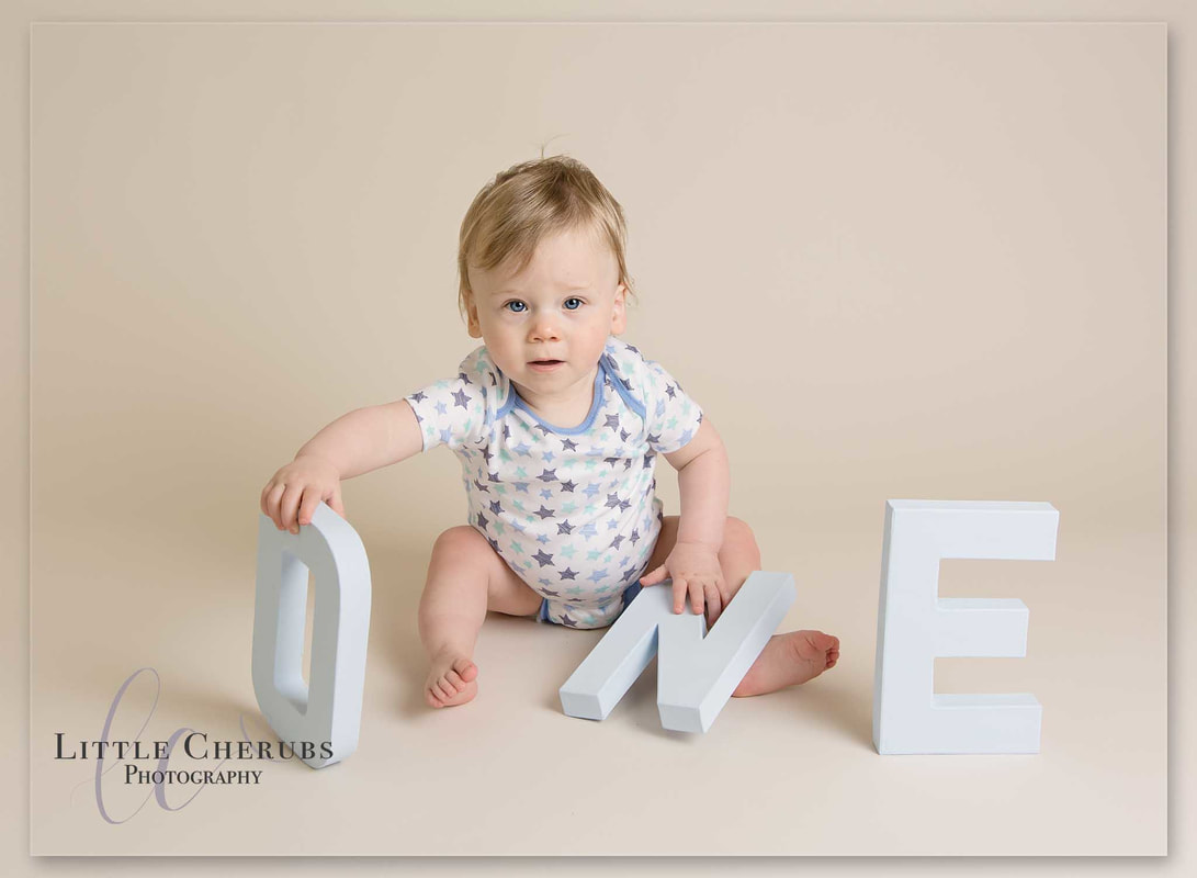 first birthday baby holding ONE letters cake smash photography cambridge little cherubs