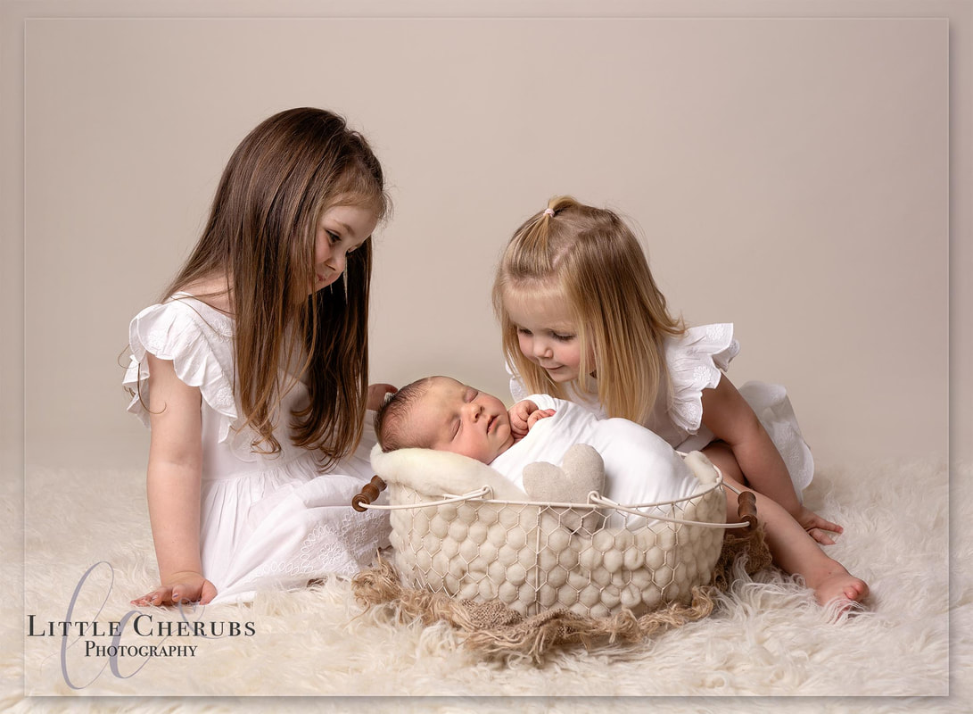 sweet sisters looking at newborn baby brother professsional sibling family portraits new baby photographer peterborough