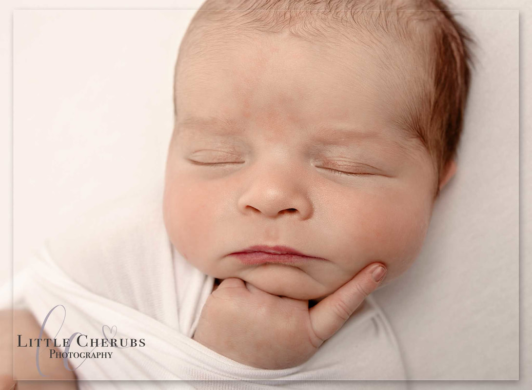 newborn baby on white with finger on face sleeping deep in thought cute new baby pictures little cherubs march cambridge chatteris photographer