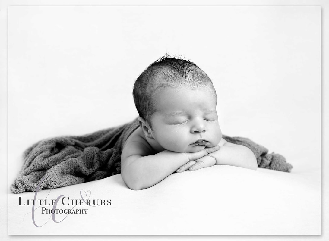 black and white picture of new baby boy on his hands asleep peterobough cambridge newborn photographer little cherubs photography