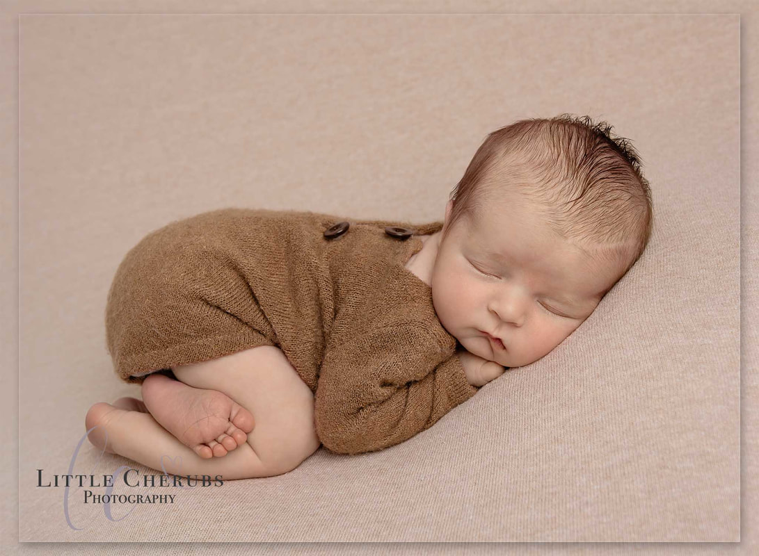 New baby boy sleeping on front in brown romper with buttons cambridge newborn photographer little cherubs photography
