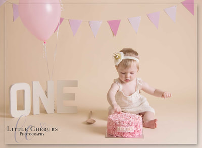 sweet baby in crown picking at birthday cake first photo shoot cake smash photographer little cherubs march cambridgeshire